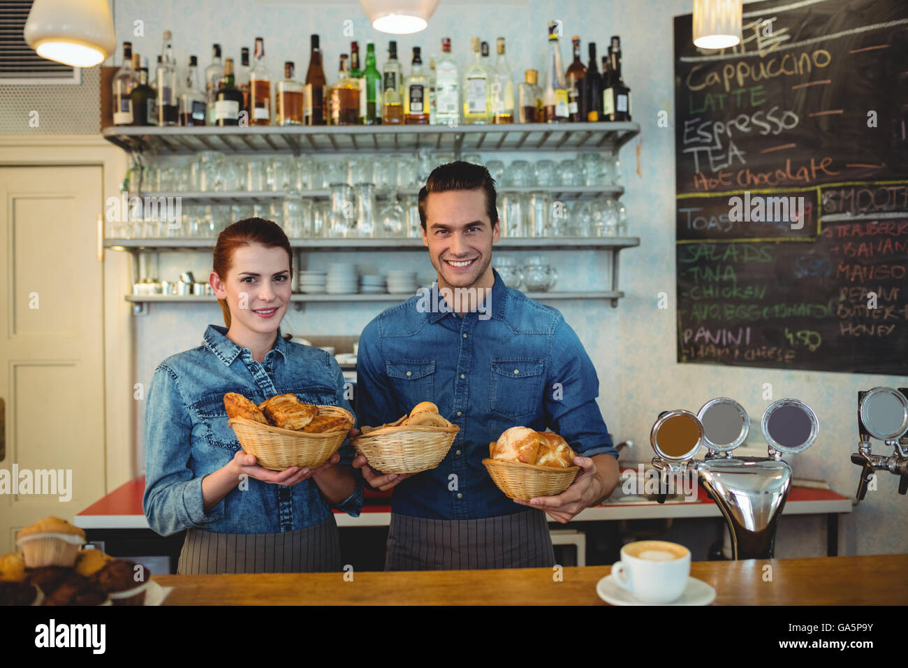 Portrait of happy co-workers with breads at cafe - Stock Image