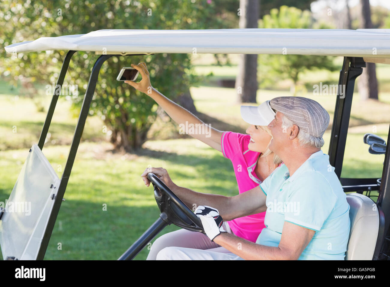 Couple taking self portrait while sitting in golf buggy - Stock Image