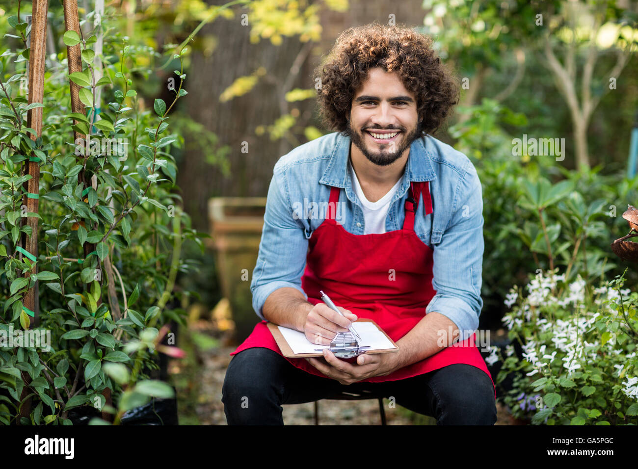 Male gardener writing on clipboard while sitting at greenhouse - Stock Image
