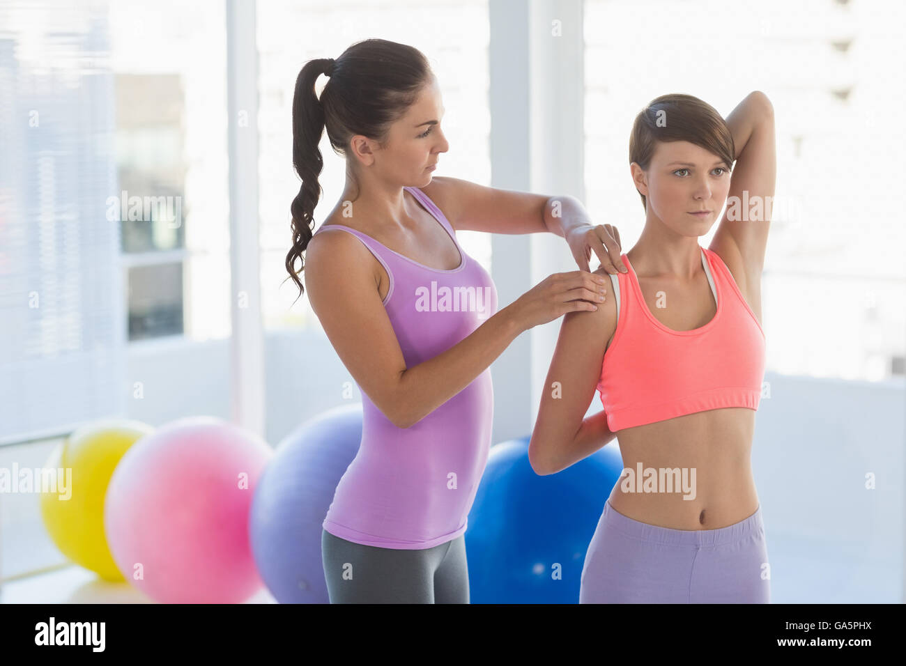 Trainer guiding woman - Stock Image