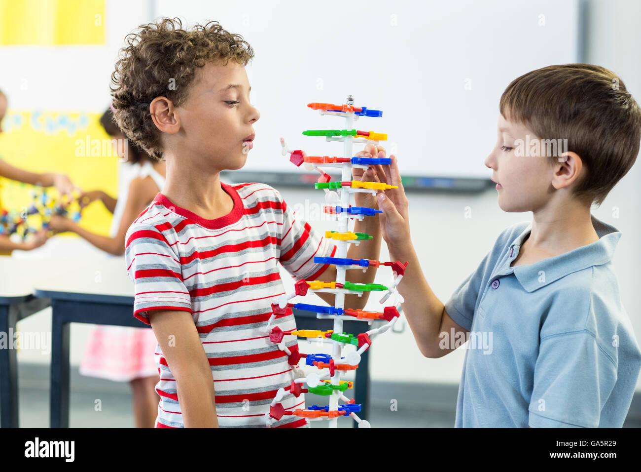 Boys observing at DNA model - Stock Image