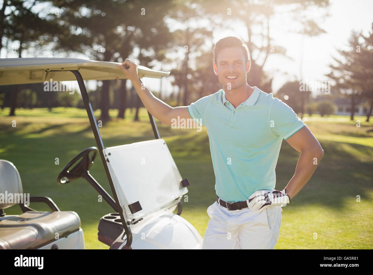 Portrait of smiling young man by golf buggy - Stock Image