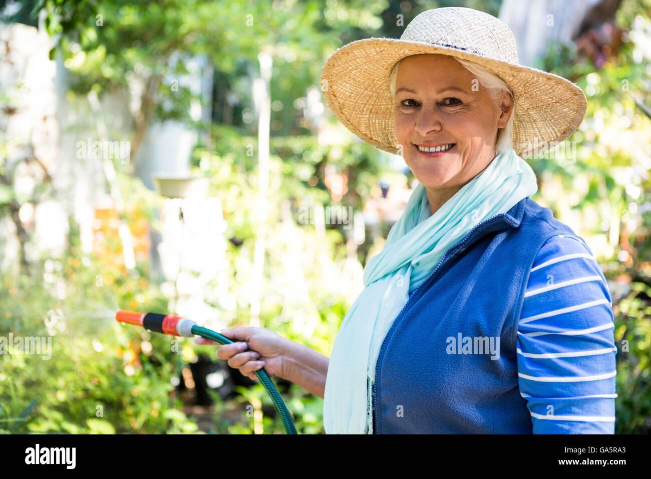 Portrait of happy gardener watering from hose at garden - Stock Image