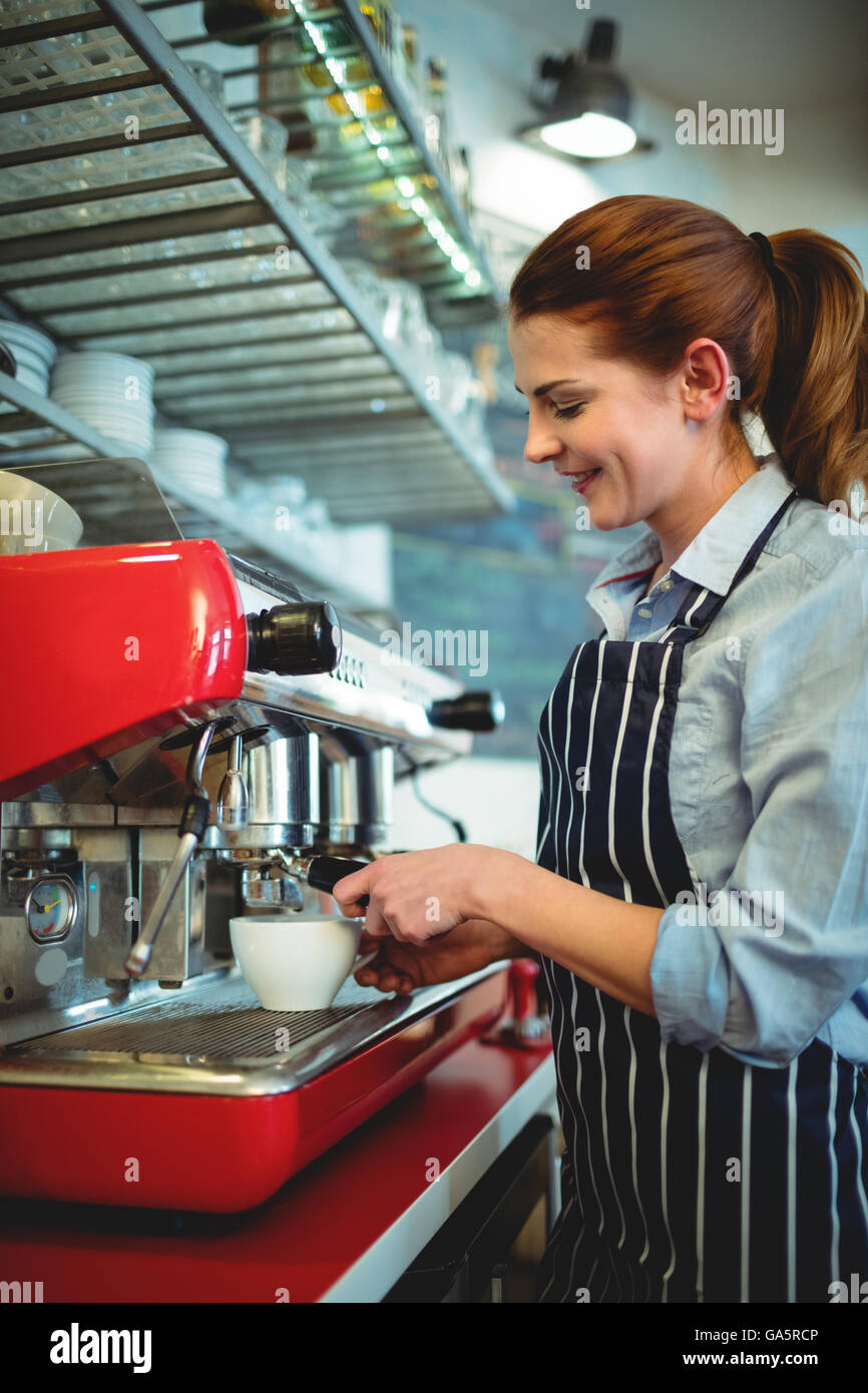Happy owner using coffee maker at cafe - Stock Image