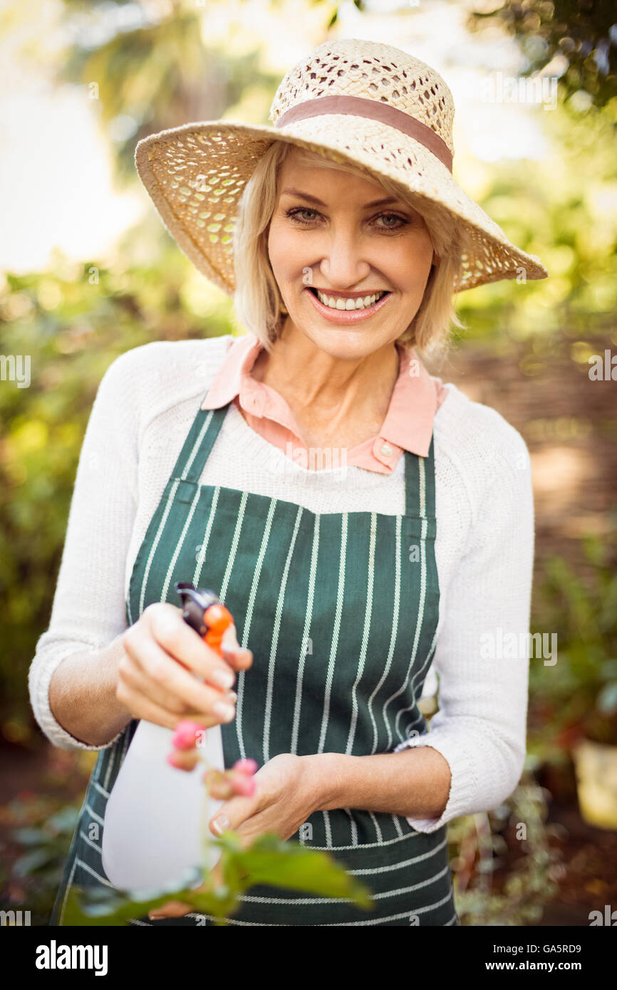 Woman smiling while watering plants - Stock Image