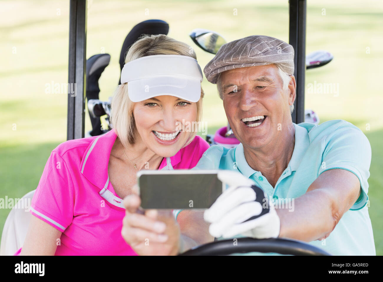 Mature couple taking selfie while sitting in golf buggy - Stock Image