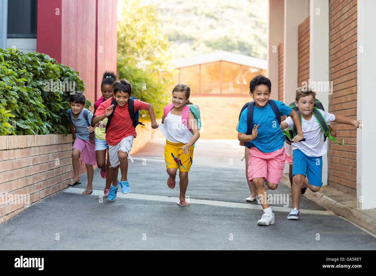 Schoolchildren running on footpath - Stock Image