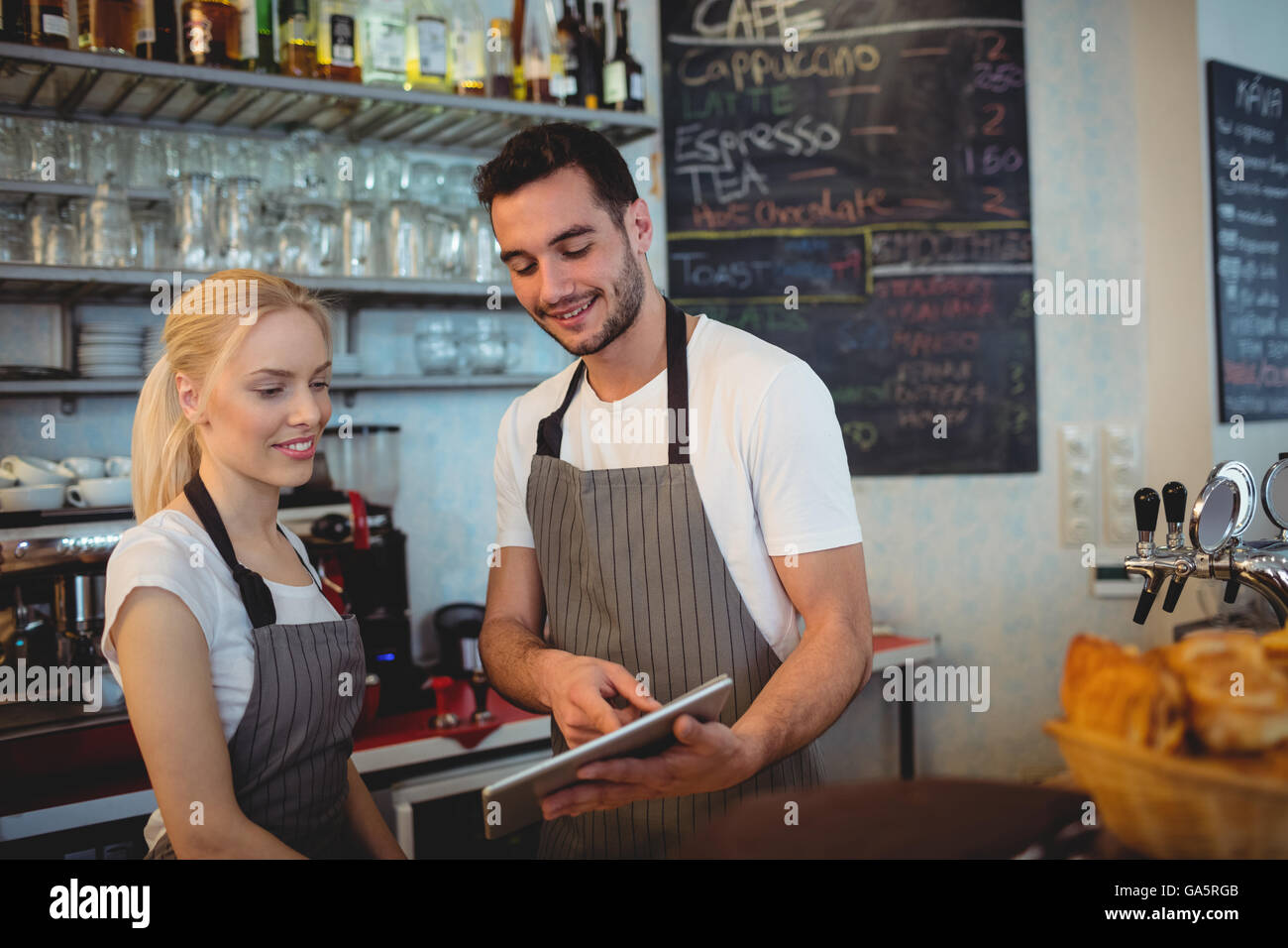 Happy co-workers using digital tablet - Stock Image