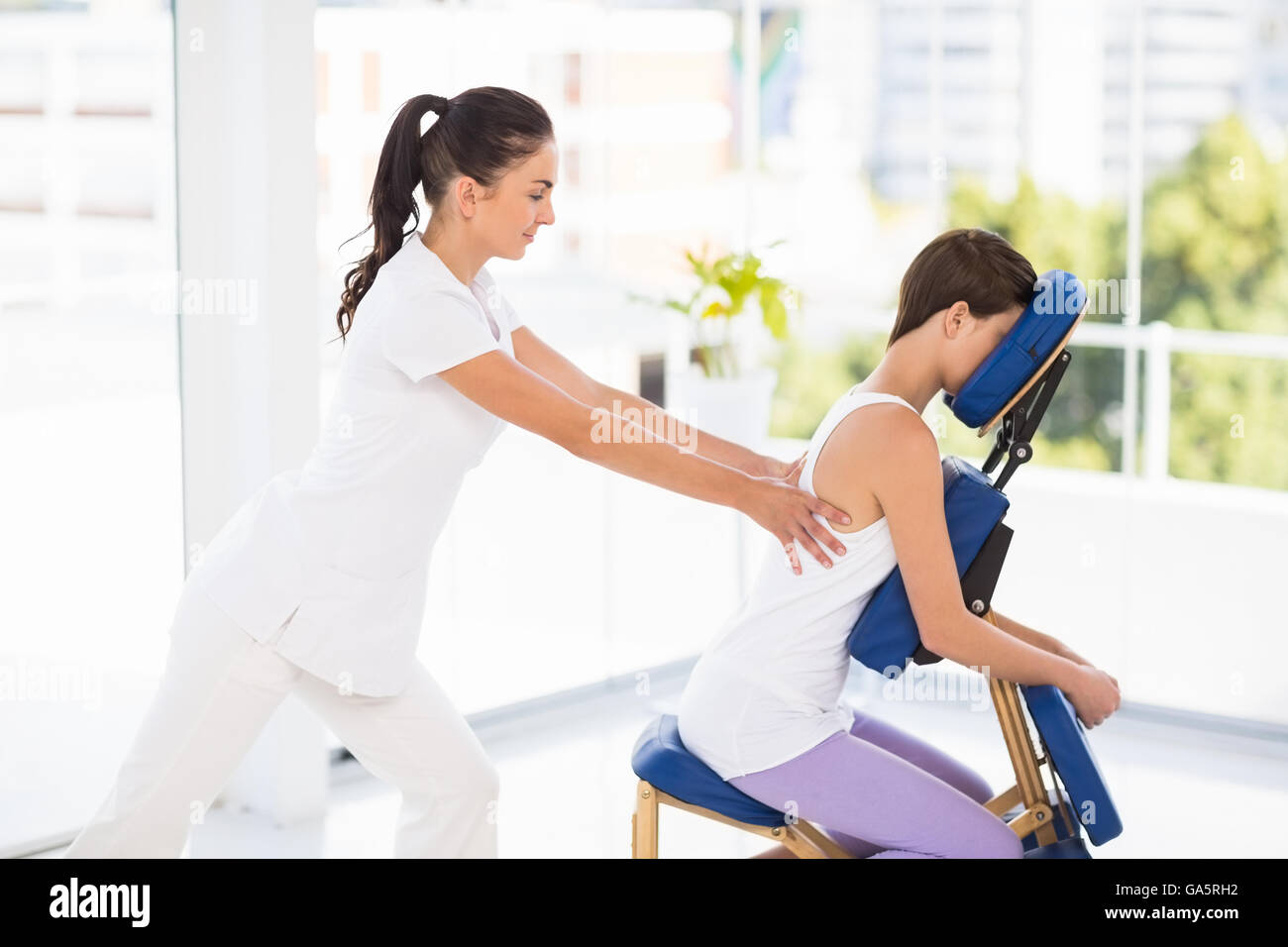 Woman being massaged on chair by masseuse - Stock Image