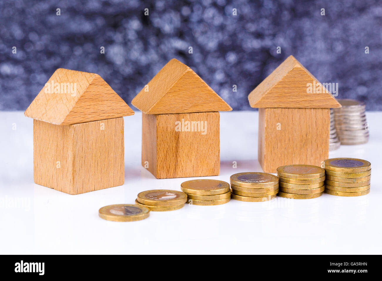 Wooden block houses and coin stacks in a row - Stock Image