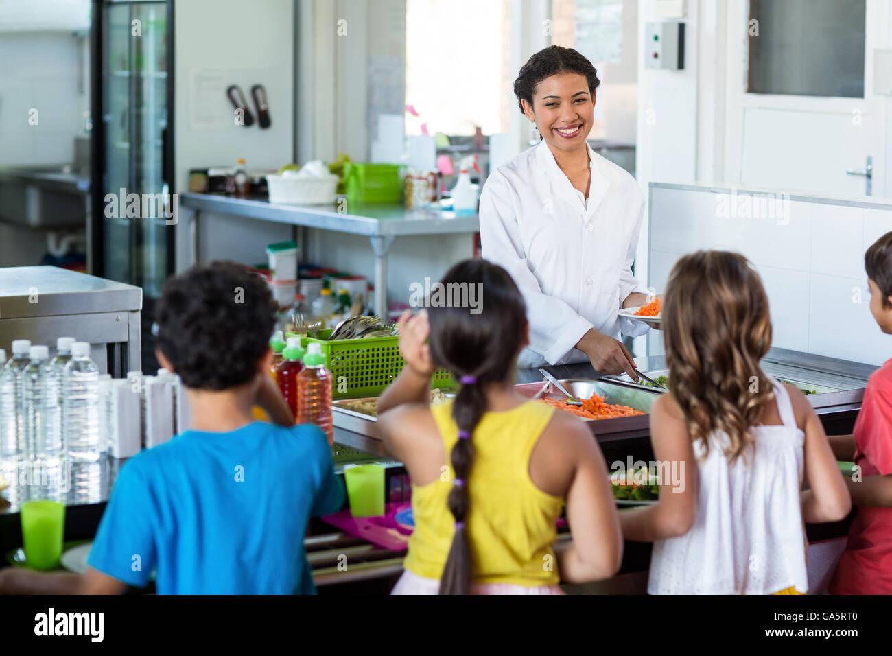 Woman serving food to schoolchildren - Stock Image