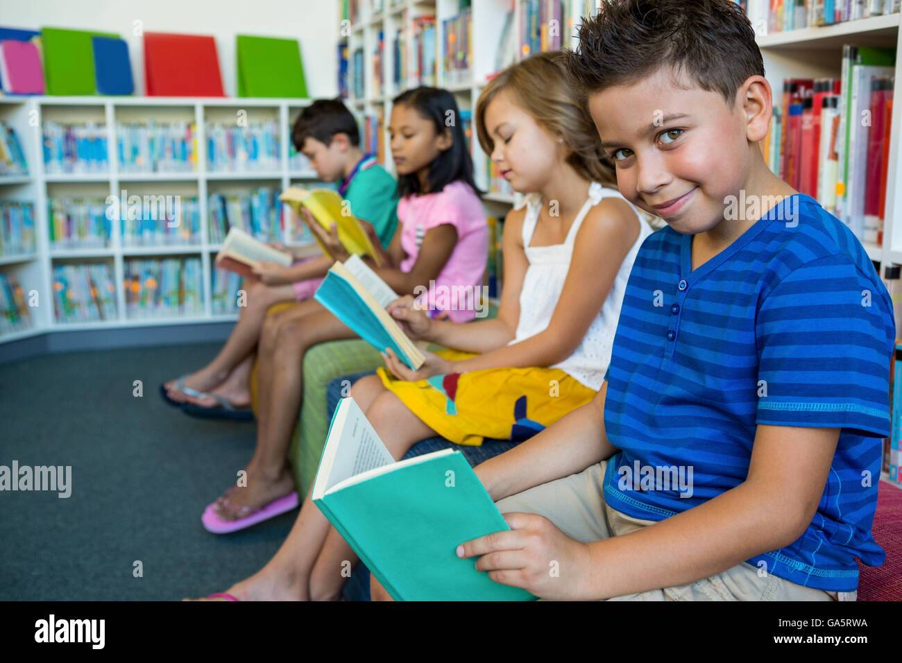Elementary students reading books in library - Stock Image