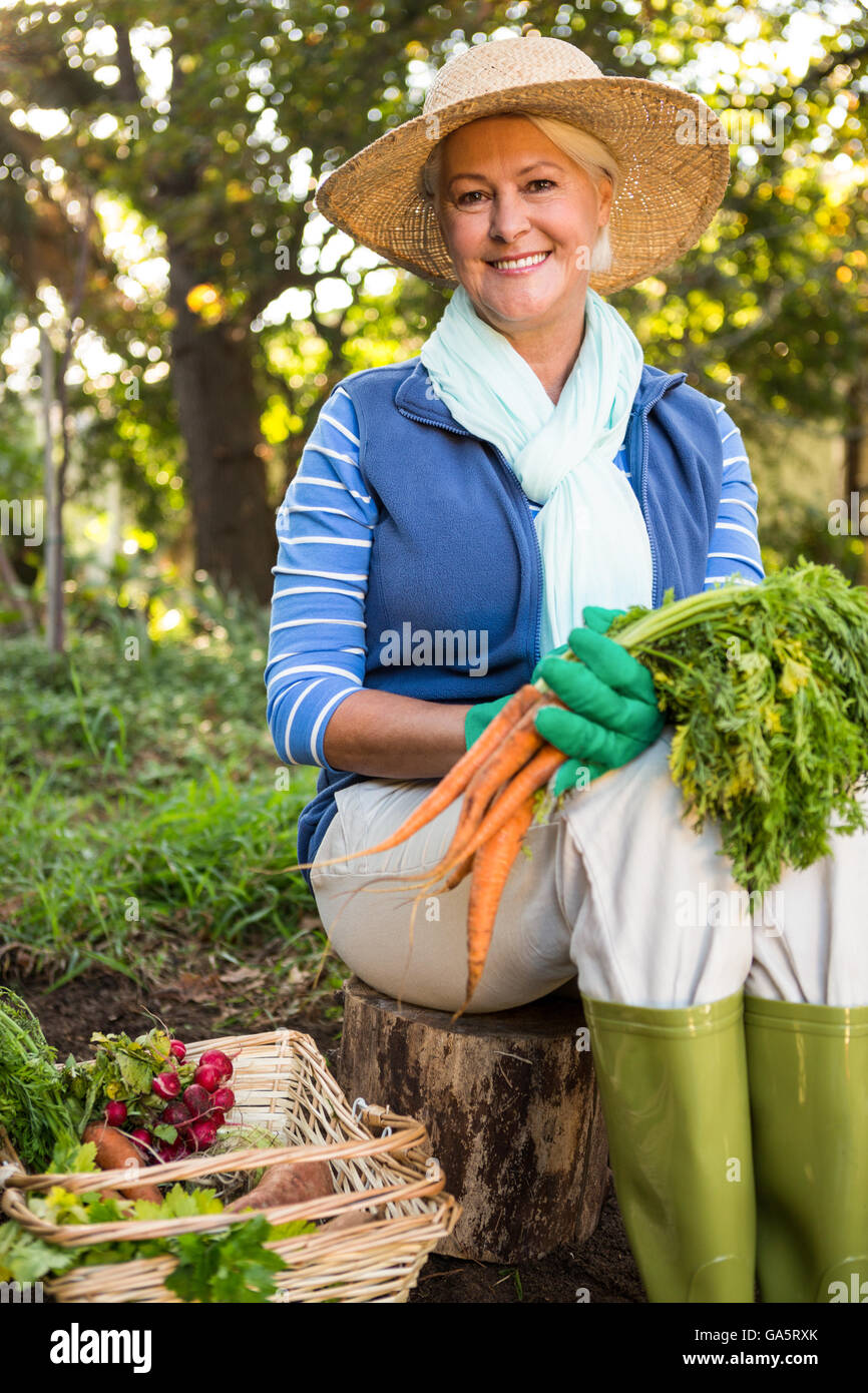 627b0b7faa5ac Portrait of happy gardener with carrots sitting at garden - Stock Image