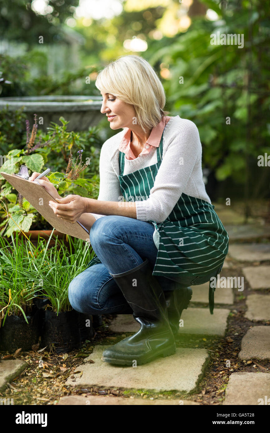 Mature woman examining plants - Stock Image