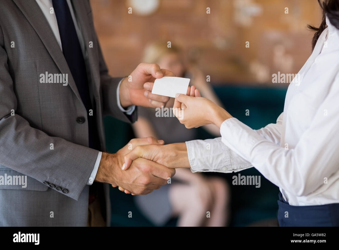 Business colleagues exchanging business card - Stock Image