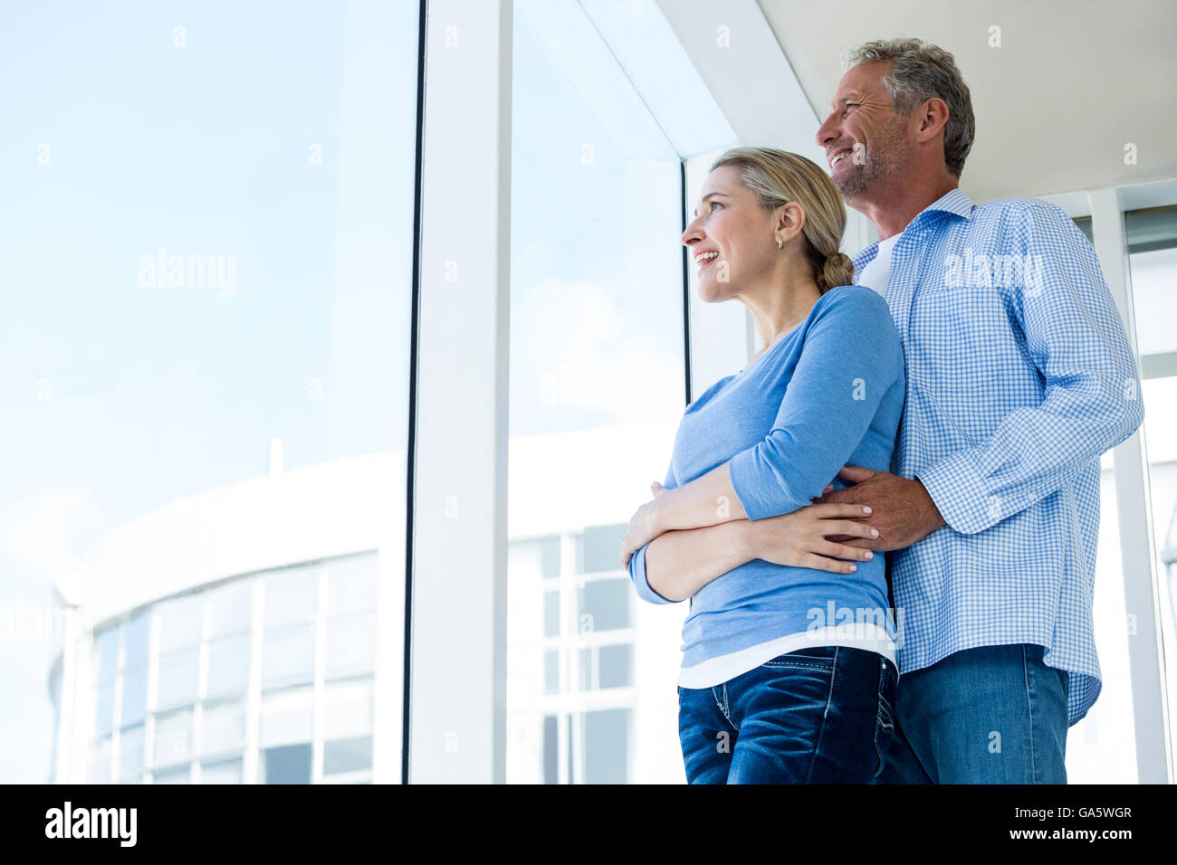 Couple looking through window at home - Stock Image