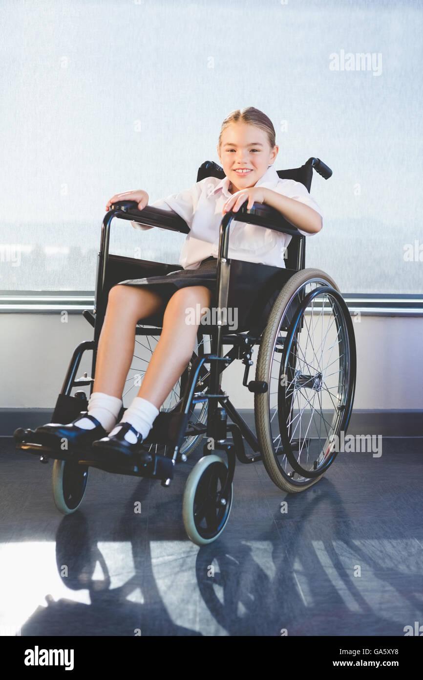 Portrait of schoolkid sitting on wheelchair - Stock Image