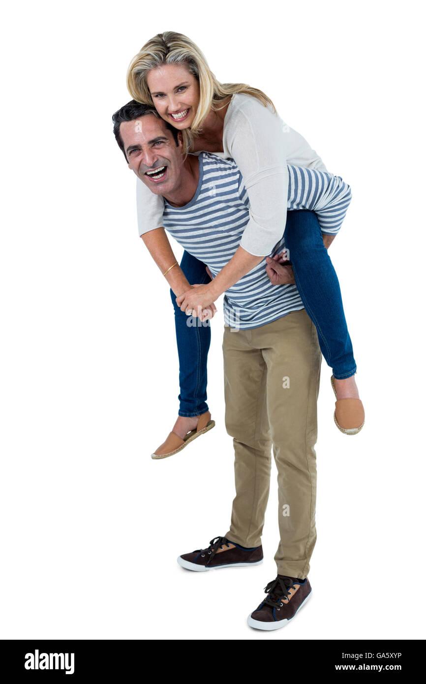 Happy man carrying woman piggyback - Stock Image