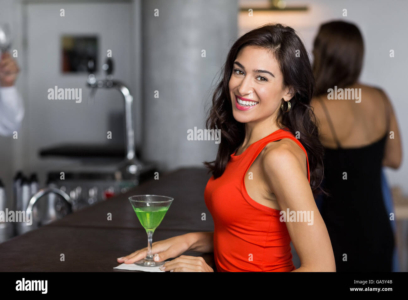 Beautiful woman standing with cocktail glass - Stock Image