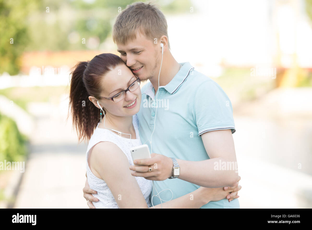 Portrait of attractive happy young couple in love standing in park, embracing, listening music on mobile phone with - Stock Image