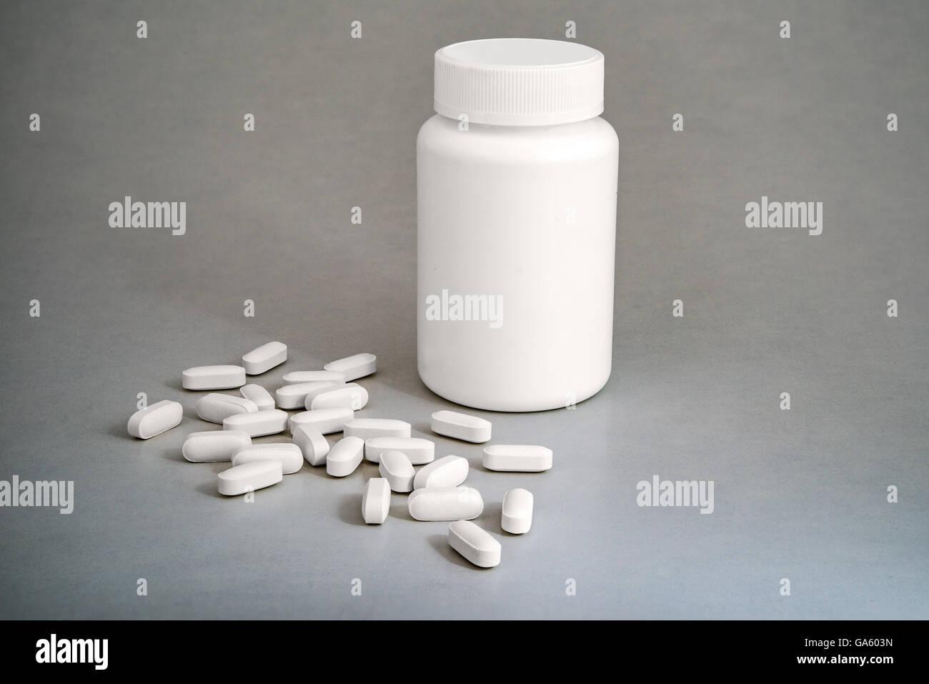 White plastic medicine bottle with white pills on gray background Stock Photo