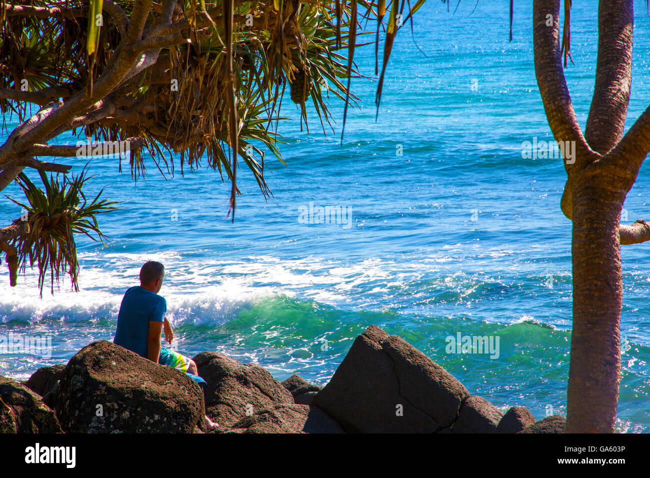Man sitting on rocks gazing at the Pacific Ocean at Burleigh Heads Australia - Stock Image