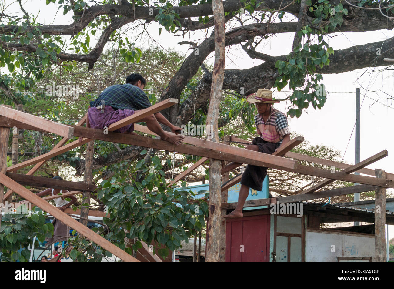 Carpenters working on a house construction site in Myanmar. - Stock Image