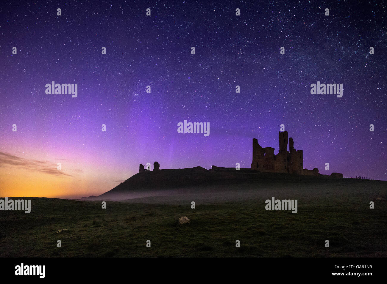 Dunstanburgh Castle at night with low mist and the northern lights dancing across the sky. - Stock Image