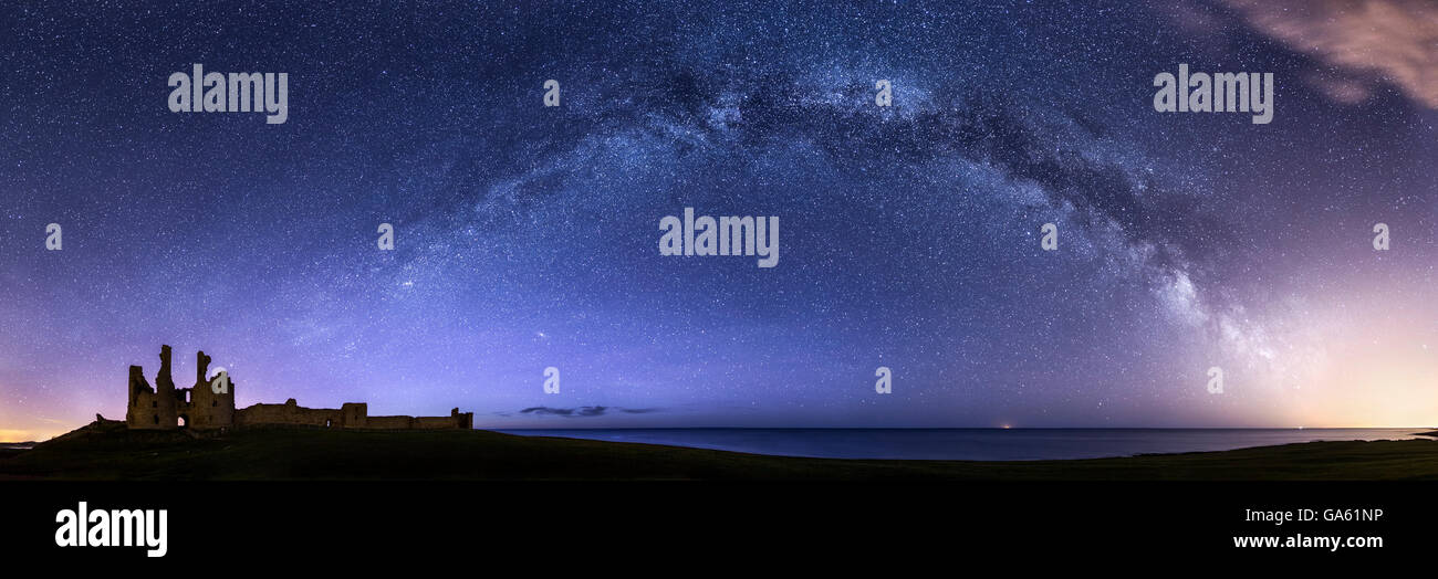 The Milky Way emerging from a blaze of light pollution and arcing over the horizon towards Dunstanburgh Castle in - Stock Image
