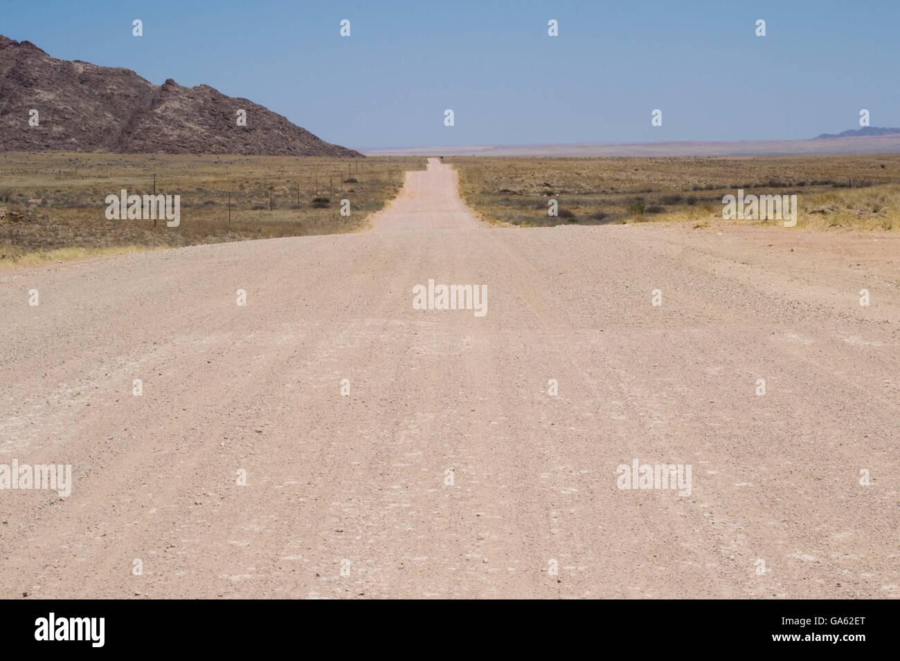 Dirt road into the desert of Namibia - Stock Image