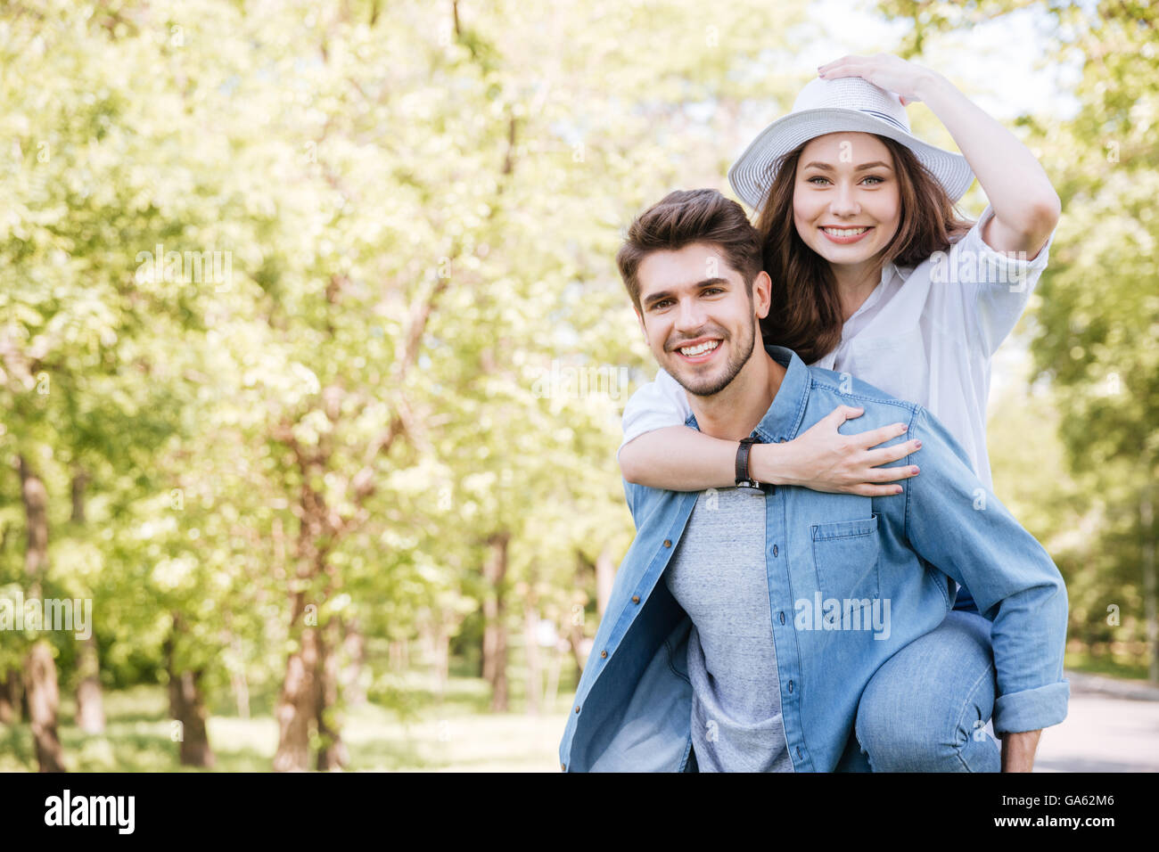Portrait of a happy young smiling couple having fun outdoors in the park - Stock Image