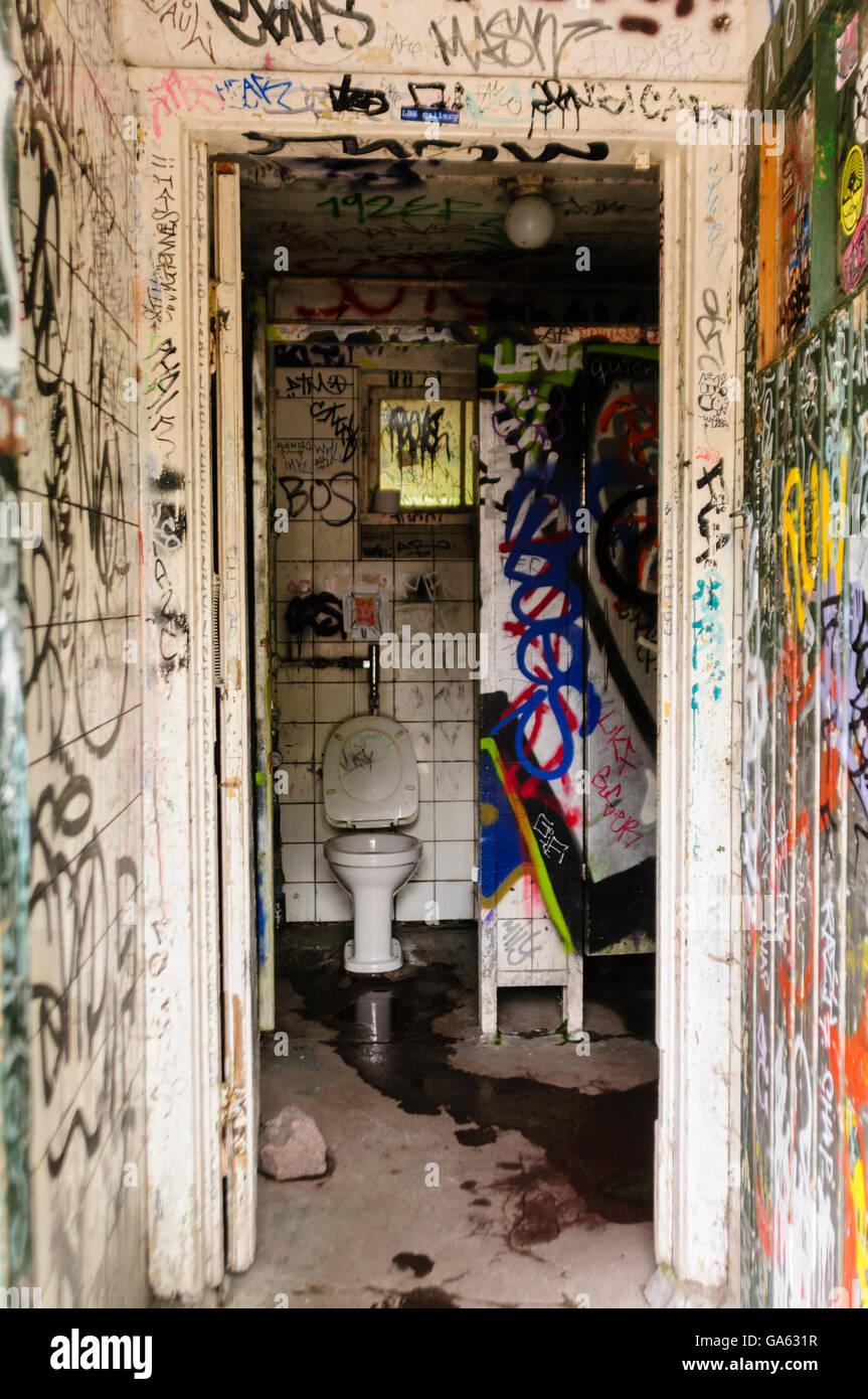 Public toilet block in Freetown Christiana, Copenhagen, covered in graffiti - Stock Image