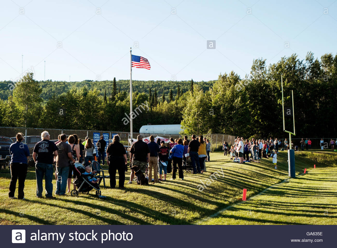 People gather for national anthem at Alumni Football Game, Cook County High School, Grand Marais, MN, on 4th of - Stock Image