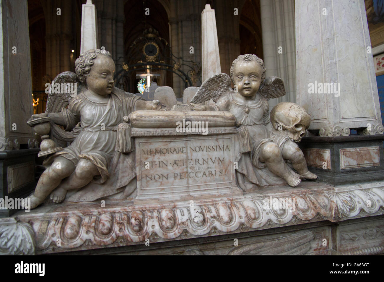 A sculpted tomb with two cherubs, one holding an hourglass and the other, a skull. Latin inscription Stock Photo