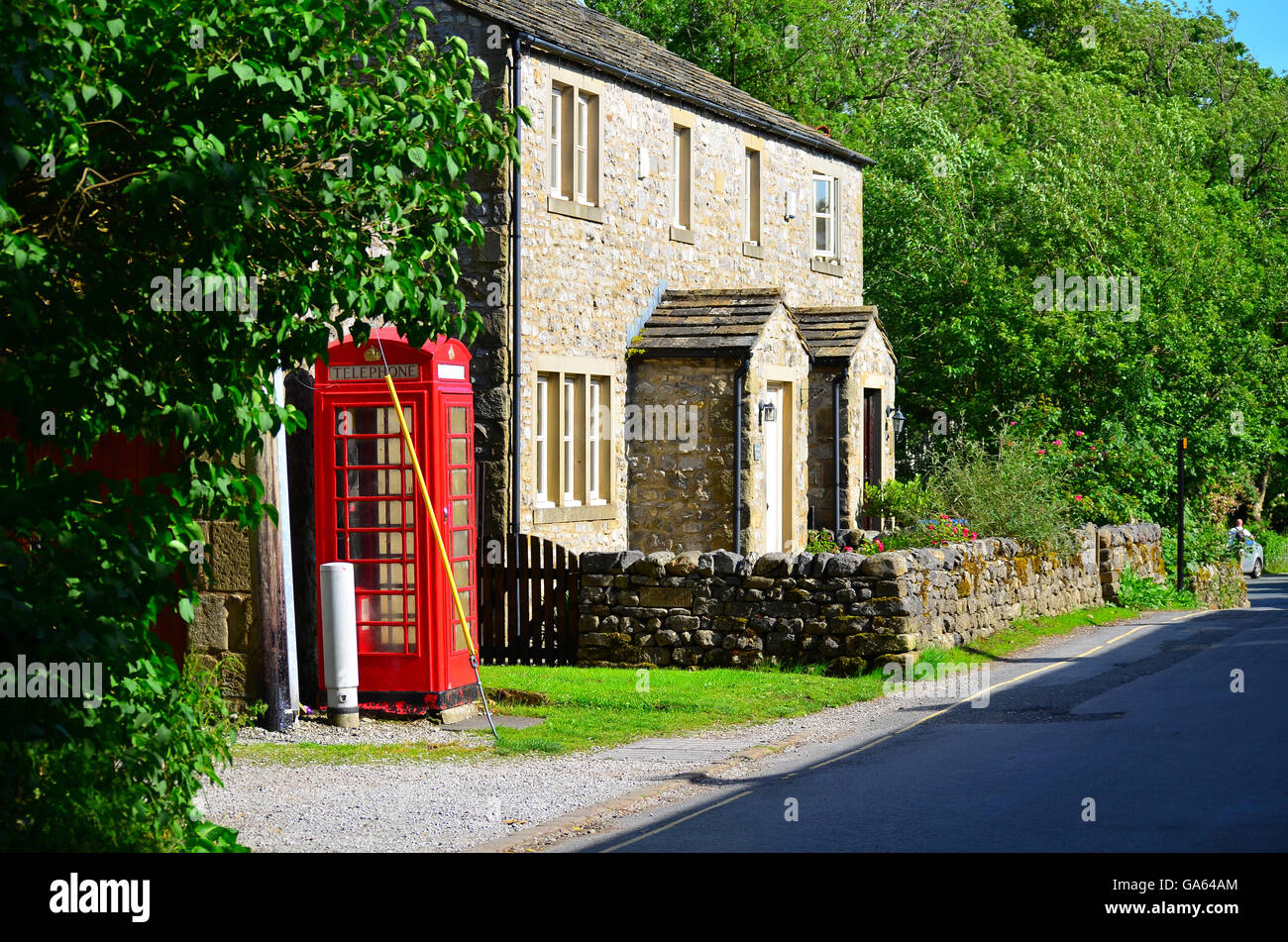 View of a red telephone box in Malham Cove, Yorkshire Dales National Park, near Settle, West Yorkshire - Stock Image