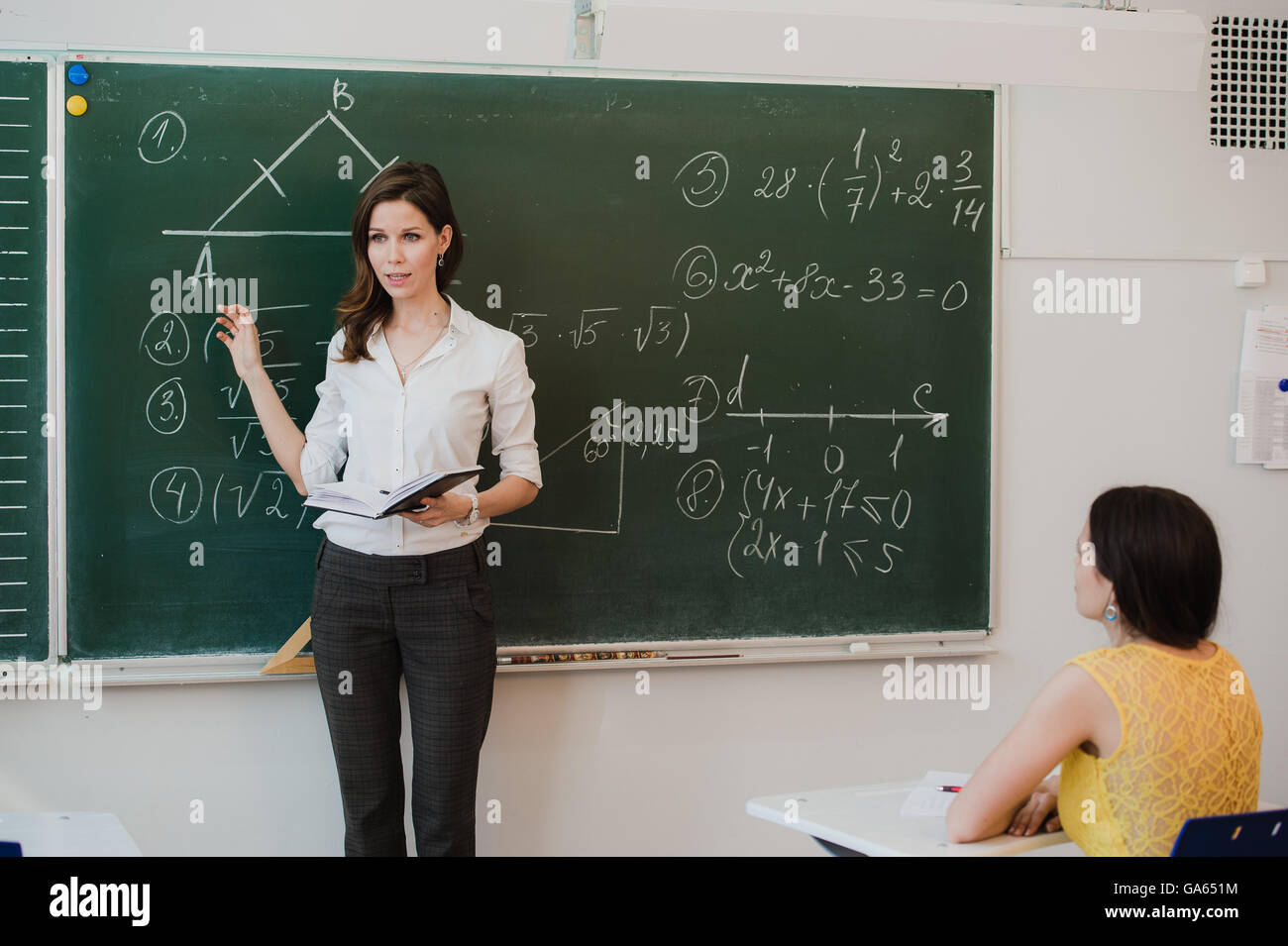 Teacher or docent or educator giving while lesson in front of a blackboard or board a sheet of paper and educate - Stock Image