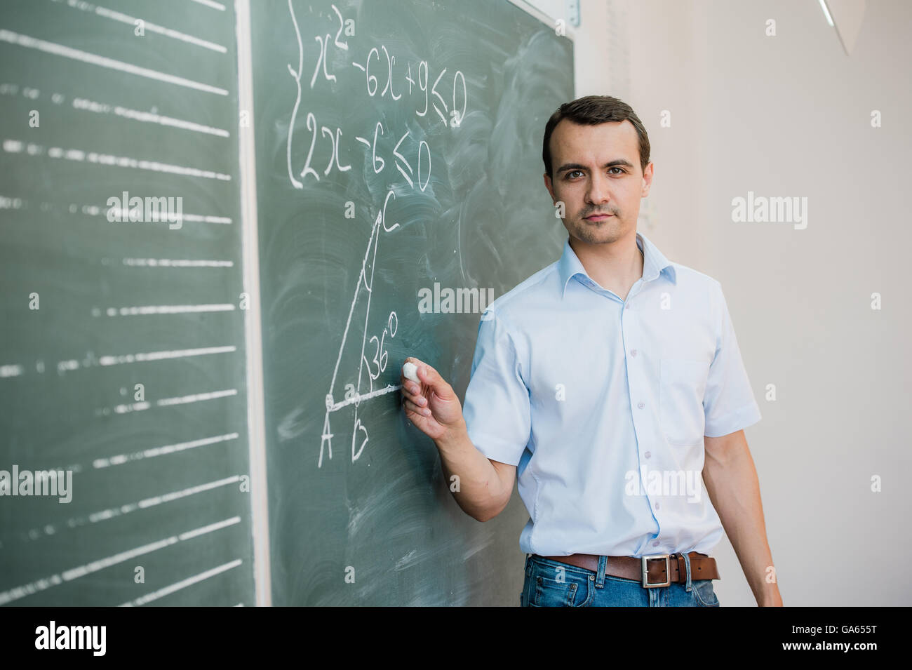 Young male teacher or student holding chalk writing on chalkboard in classroom - Stock Image