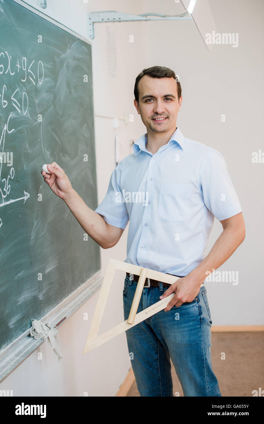 Young teacher or student holding triangle pointing at chalkboard with formula, looking to camera and smiling - Stock Image