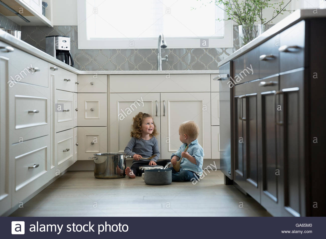 Brother and sister playing with pots and pans on kitchen floor - Stock Image