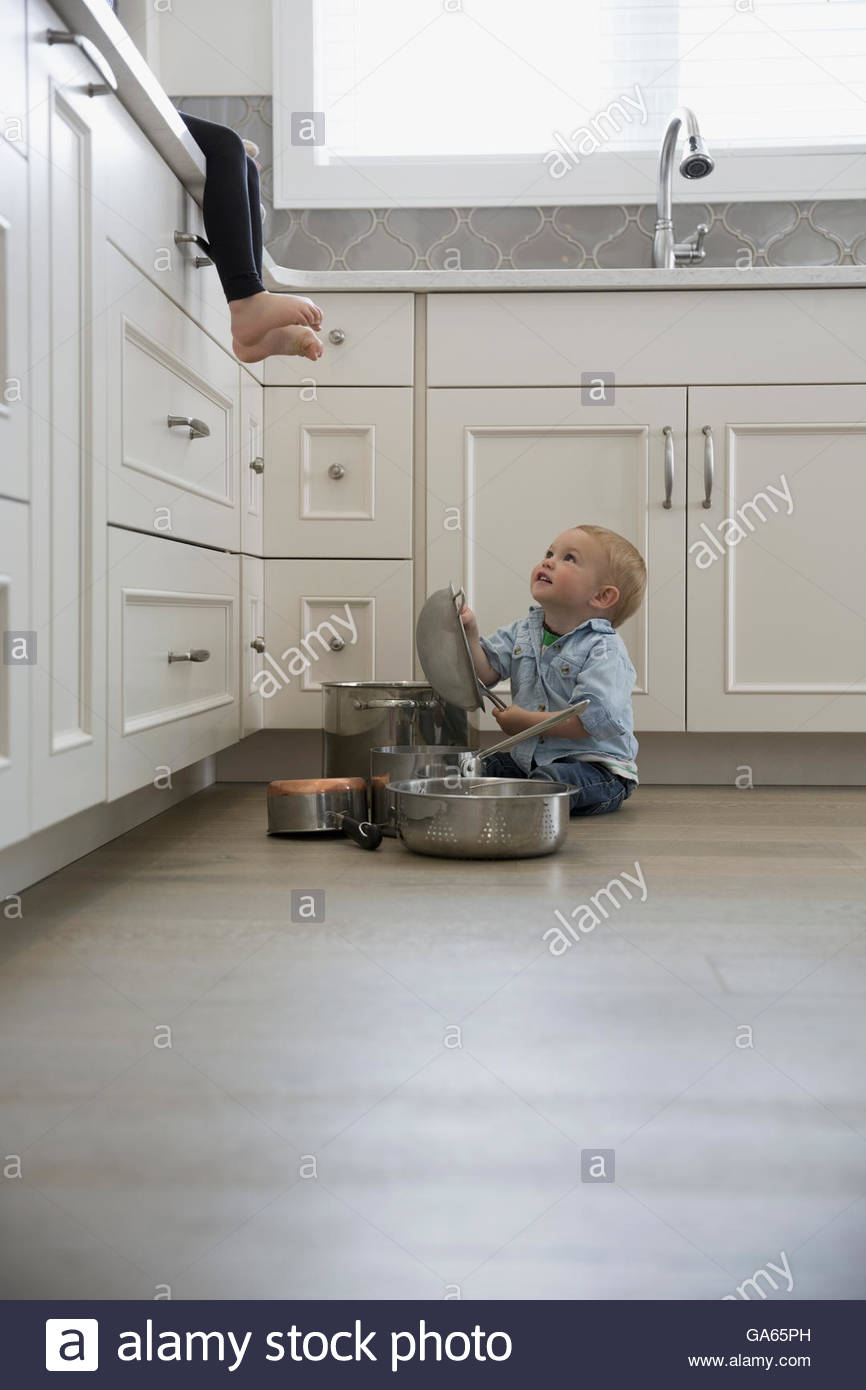 Baby boy playing with pots and pans on kitchen floor - Stock Image