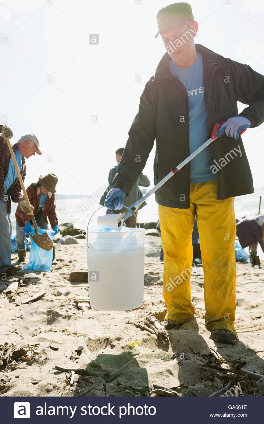 Beach cleanup volunteer using claw to pick up litter on beach - Stock Image