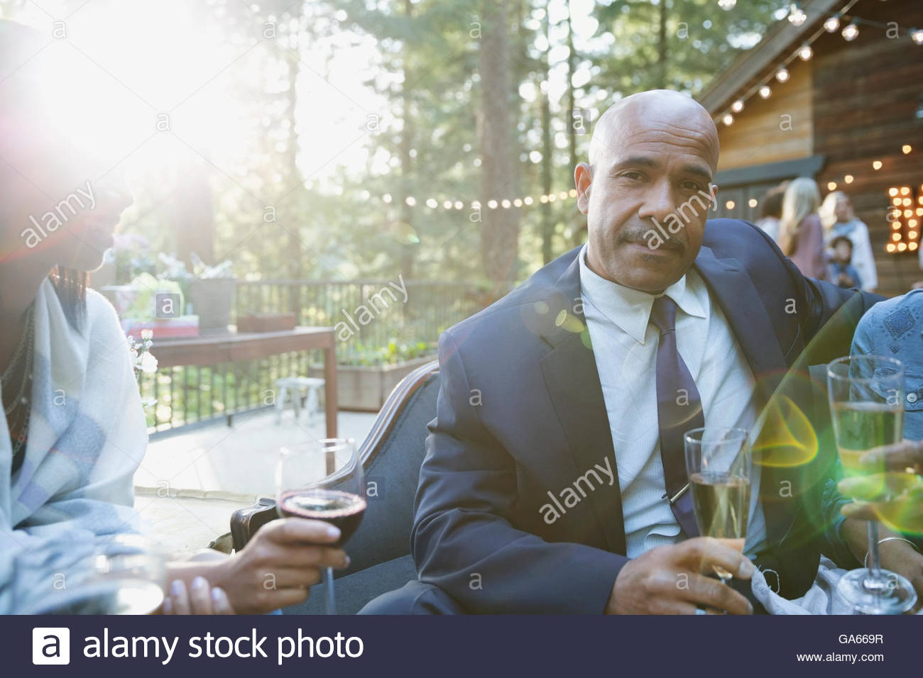 Portrait well-dressed man drinking champagne at party on sunny cabin balcony - Stock Image