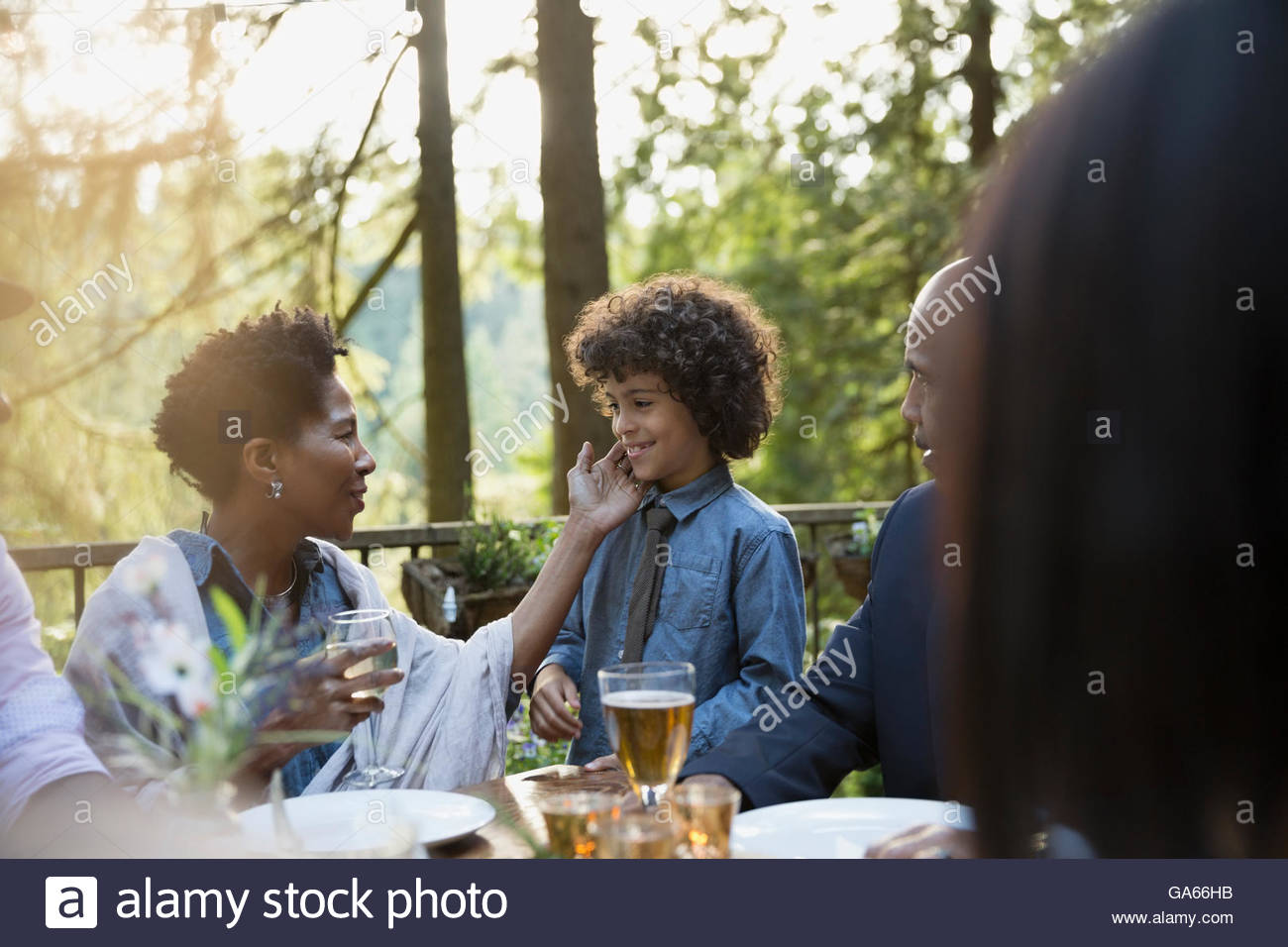 Affectionate grandmother and grandson at dinner party - Stock Image