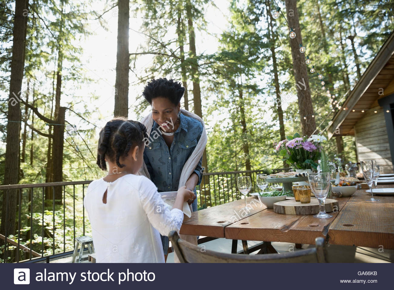 Granddaughter helping grandmother prepare dinner party on cabin balcony in woods - Stock Image