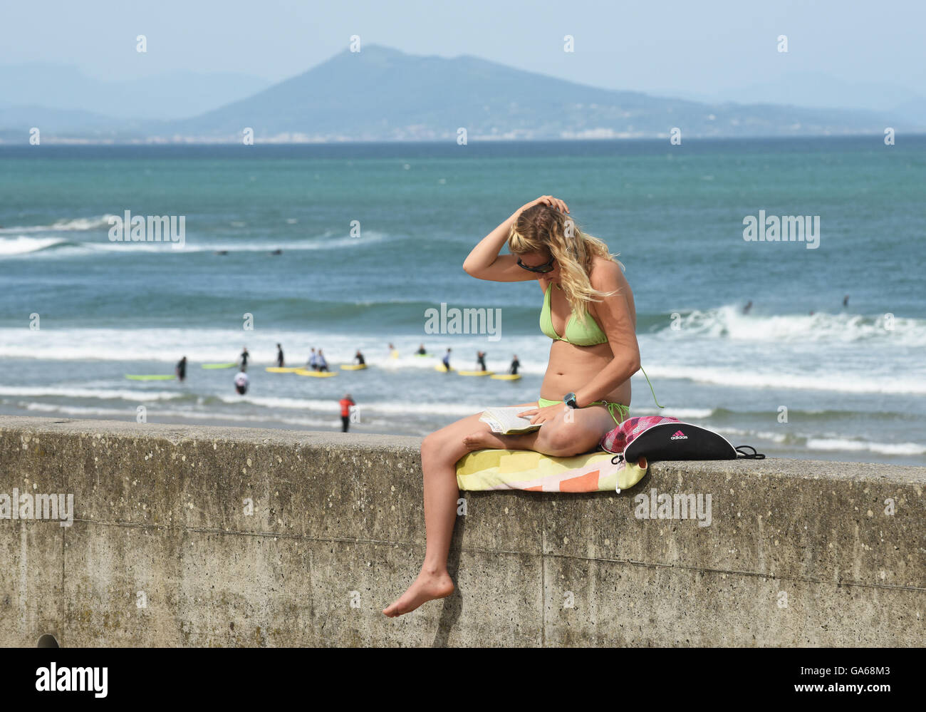 Woman girl female reading holiday book Biarritz France - Stock Image