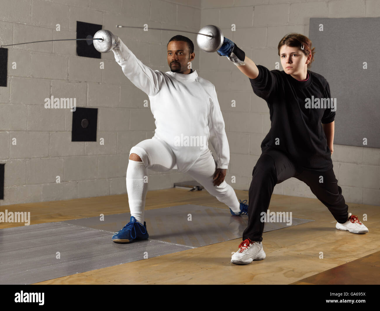 Coach and a teenage student practicing fencing in a gym Stock Photo
