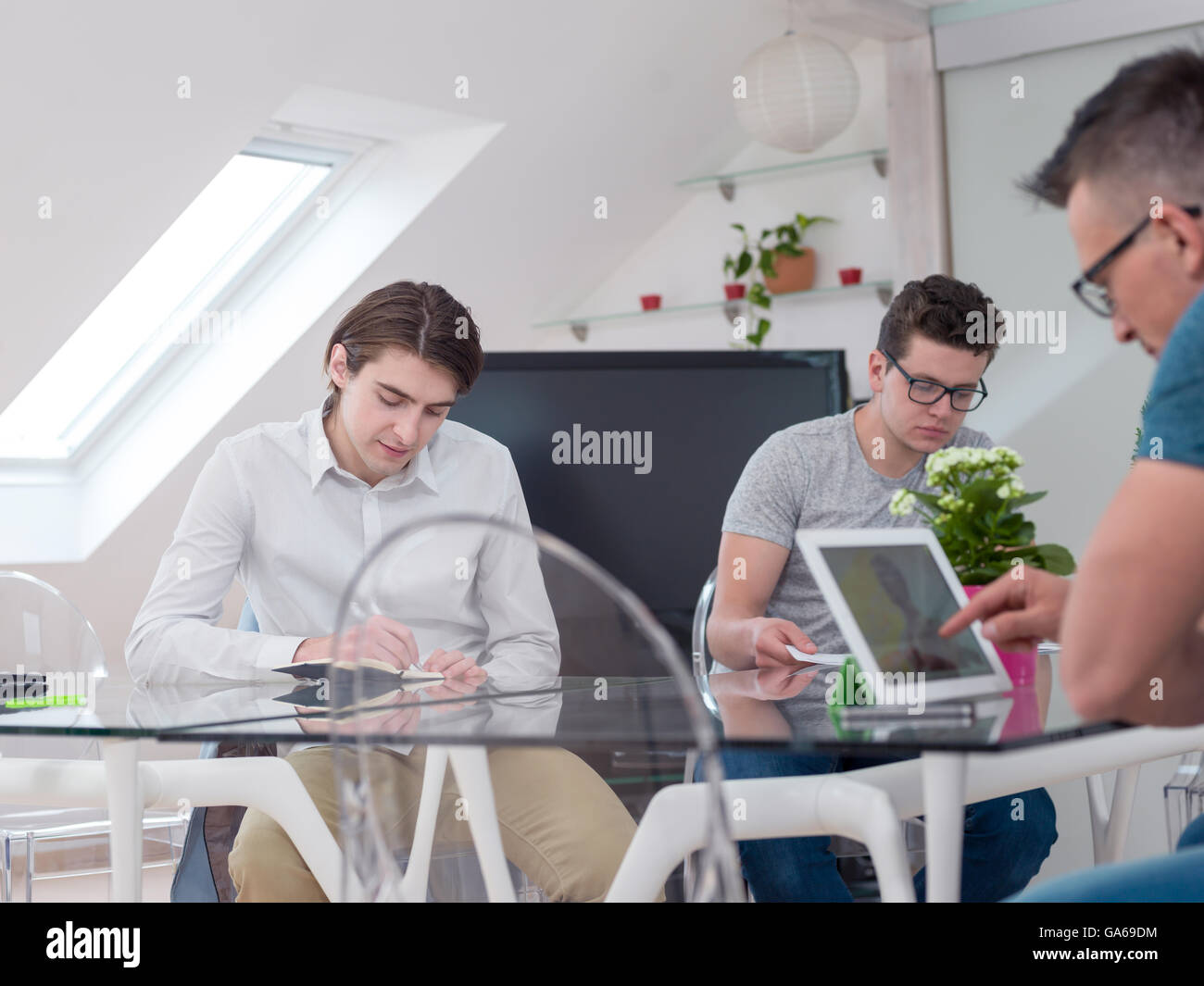 Making great decisions. Young people staring a new business and discussing something with their colleagues at office - Stock Image