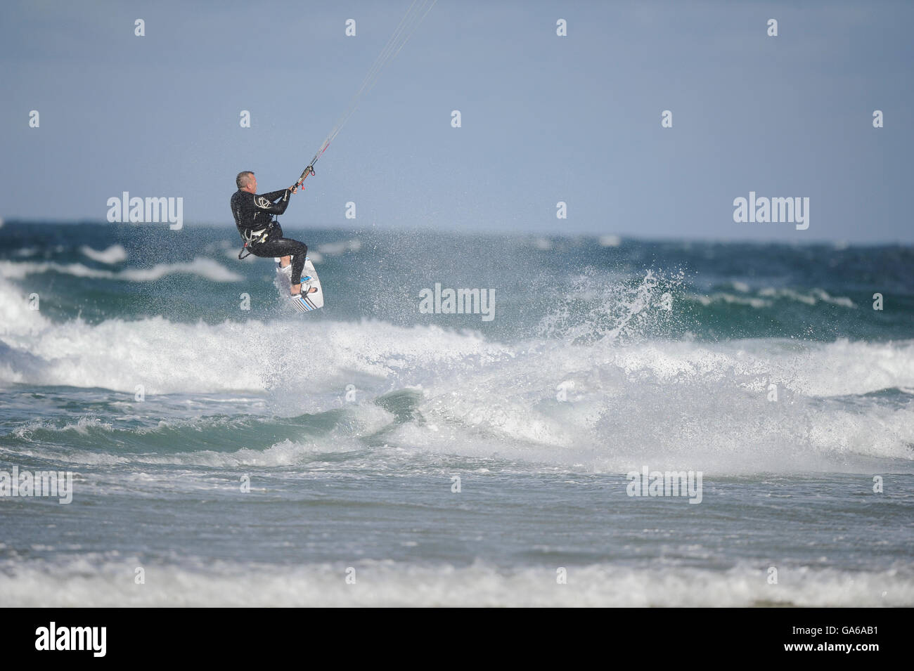 Kitesurfer launching off a wave with spray splashing off the baord - Stock Image