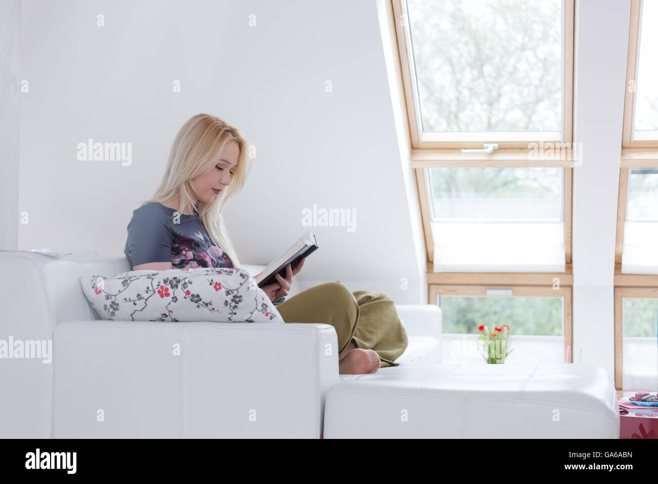 Young Woman Sitting In An Armchair And Reading A Book