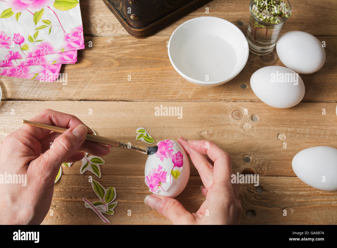 Apply woman PVA glue on colored Easter egg, with the technique of decoupage Stock Photo